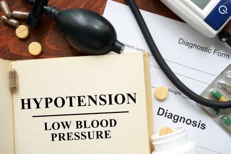 hypotension: Low blood pressure Hypotension written on a book. Medical concept. Stock Photo