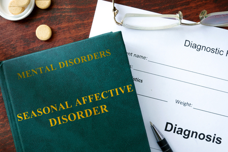 winter blues: Seasonal affective disorder  concept. Diagnostic form and book on a table.
