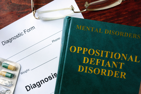 oppositional: Oppositional defiant disorder  concept. Diagnostic form and book on a table.