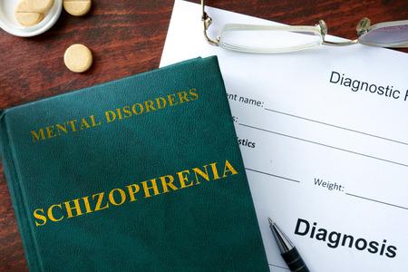 esquizofrenia: Concepto de la esquizofrenia. Forma de diagn�stico y el libro sobre la mesa. Foto de archivo