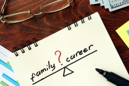 prioritizing: Words Career and family balance   written in the notepad.