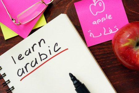 distance learning: Words learn arabic written in the notepad. Stock Photo