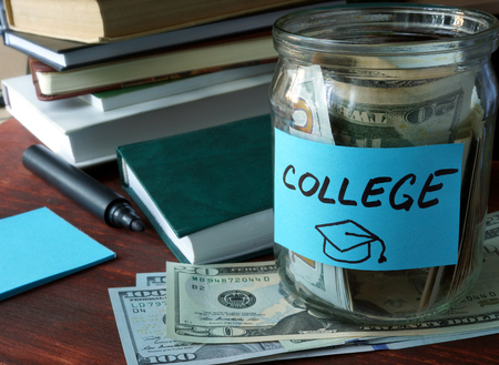 Jar with label college and money on the table.