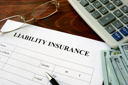 Liability insurance  form and dollars on the table. 스톡 콘텐츠
