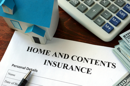 Home and contents insurance form and dollars on the table.
