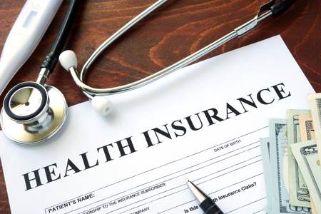 health issue: Health insurance  form and dollars on the table.