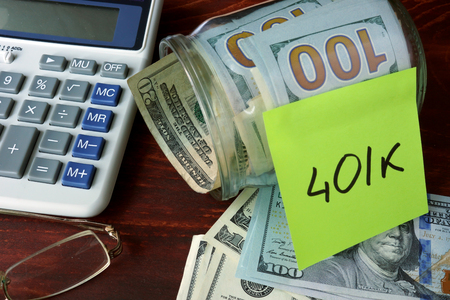 personal finance: Jar with label 401k and money on the table.