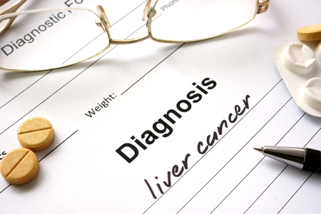 Diagnosis liver cancer written in the diagnostic form and pills.