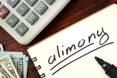 alimony: Notepad with alimony on the wooden table.