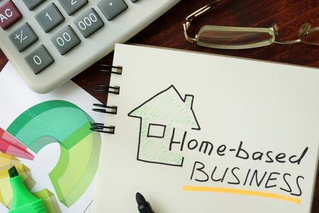 Bloc-notes avec les entreprises à domicile sur la table en bois. Banque d'images