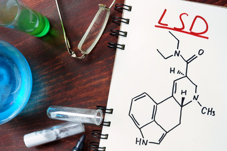 lsd: Notepad with chemical formula of LSD on the wooden table. Drugs concept.