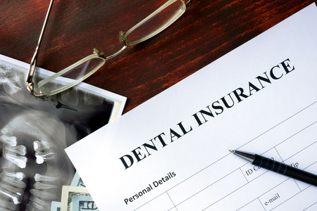 dientes: Formulario de seguro dental en la mesa de madera.