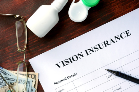 eye exam: Vision insurance form on the wooden table.