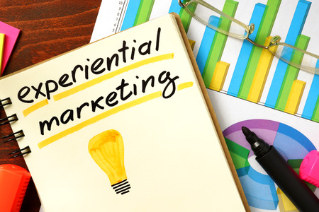 experiential: Notepad with experiential marketing on the wooden table.