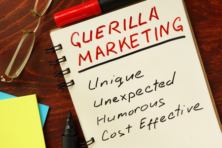 guerilla: Notepad with guerilla marketing on the wooden table.