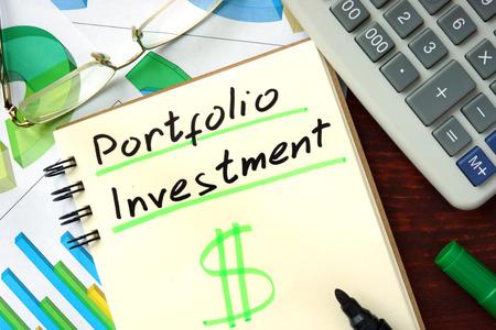 ポートフォリオ投資概念。テーブルの上のメモ帳。