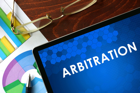arbitration: Tablet with arbitration on a table. Business concept.