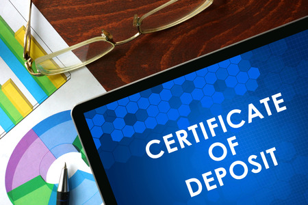 deposit: Tablet with certificate of deposit CD on a table. Business concept. Stock Photo