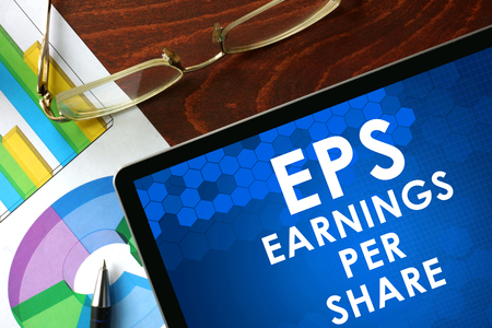 Tablet with earnings per share EPS on a table. Business concept.