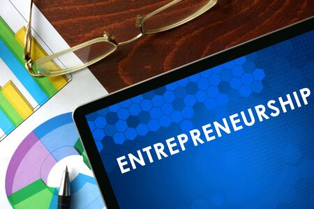 company person: Tablet with entrepreneurship on a table. Business concept. Stock Photo