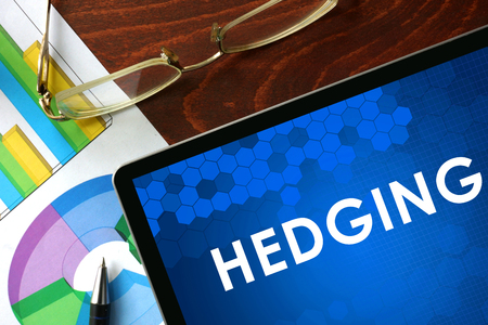 hedging: Tablet with hedging on a table. Business concept. Stock Photo
