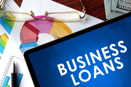 loans: Tablet with business loans on a table. Stock Photo