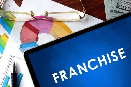 franchise: Tablet with franchise on a table. Stock Photo