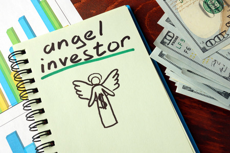 investor: Notebook with angel investors  sign.  Business concept. Stock Photo
