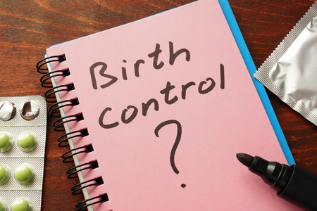 safe sex: Notebook with the words  Birth control on the table. Stock Photo