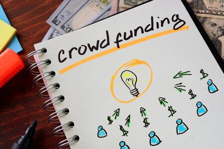 crowd sourcing: Notebook with crowd funding  sign on a table. Business concept.