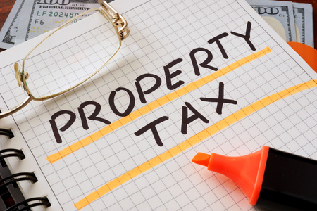 固定資産税とノートブックはテーブルにサインオンします。ビジネス コンセプトです。