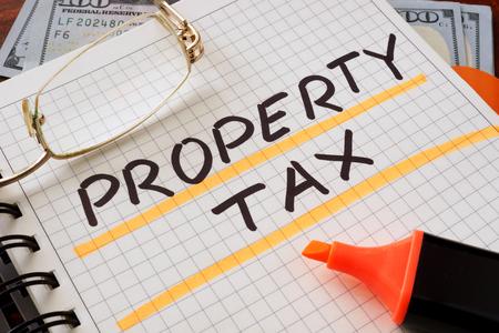 impuestos: Notebook con el signo de impuestos a la propiedad sobre una mesa. Concepto de negocio. Foto de archivo