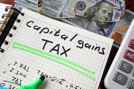 capital gains: Notebook with  capital gains tax sign on a table. Business concept.