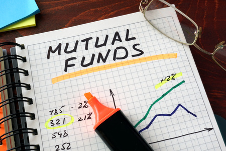 mutual funds: Notebook with  mutual funds sign on a table. Business concept.