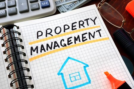 property management: Notebook with property management  sign on a table. Business concept.
