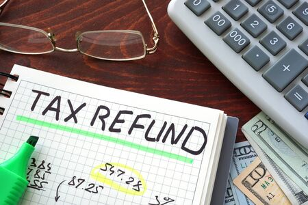 Notebook with tax refund sign on a table. Business concept. Stock Photo