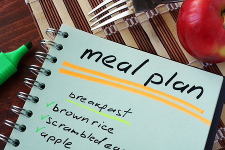Notepad with meal plan and apple. Diet planning. Archivio Fotografico