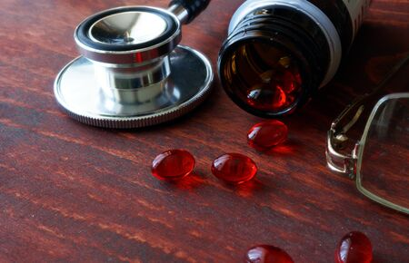 pill popping: Red capsules poured out of bottle and stethoscope. Medicines concept.