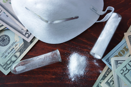 narcotics: Drugs produce and sales concept. Dollars and white powder with mask. Stock Photo