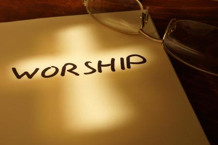Boek met woord Aanbidding, cross en glazen.