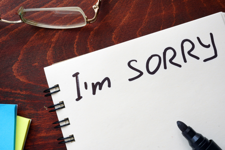 pardon: I am sorry written on notepad on a table.
