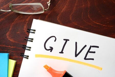 give: Give written on notepad on a table. Stock Photo