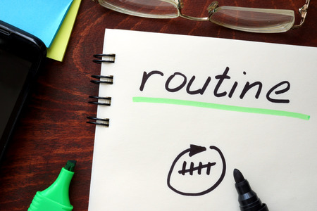 regimen: Routine written on notepad on a table. Stock Photo