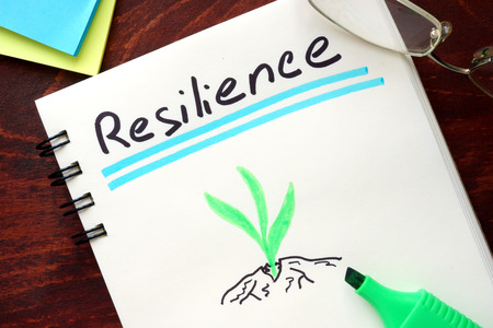 resilient: Resilience written on notepad on a table. Stock Photo