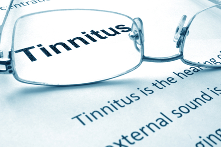 dolor de oido: Papel con diagnóstico de tinnitus y gafas. Foto de archivo