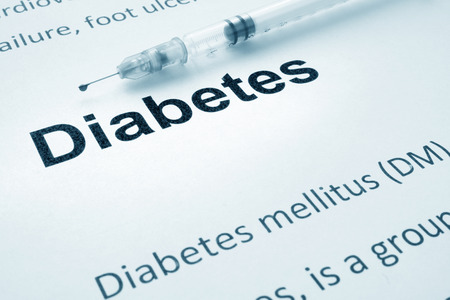 mellitus: Paper with word diabetes and syringe.