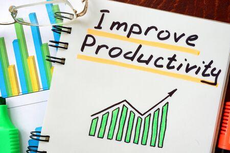 productividad: Mejorar la productividad escrito en un bloc de notas. Concepto de negocio. Foto de archivo