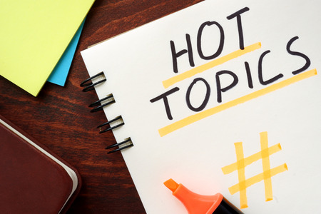 trending: Hot Topics written in a notepad on a wooden background. Stock Photo