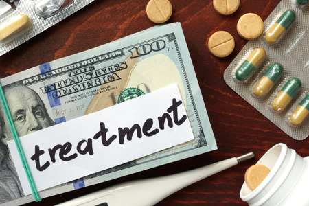 hospital expenses: Dollars and pills on a wooden table. Treatment cost concept. Stock Photo