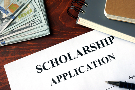 scholarship: Scholarship Application on a table and dollars.